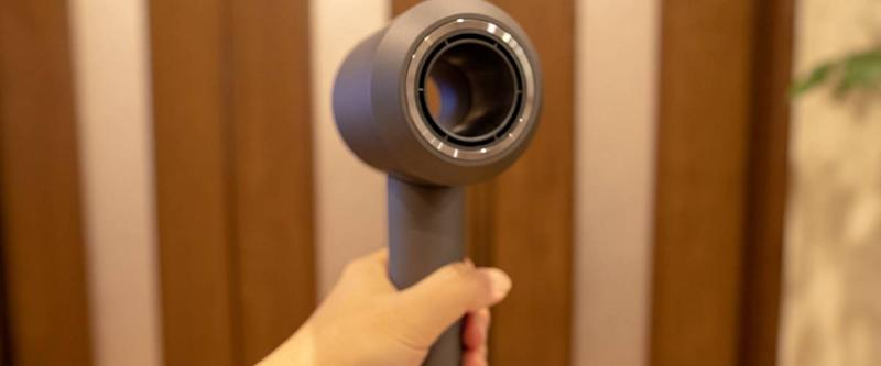 Hand holding a Dyson Supersonic hair dryer