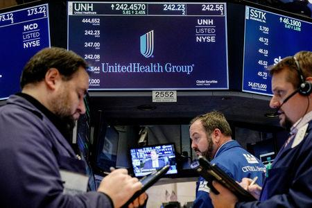 FILE PHOTO: Traders work at the post where UnitedHealth Group is traded on the floor of the NYSE in New York