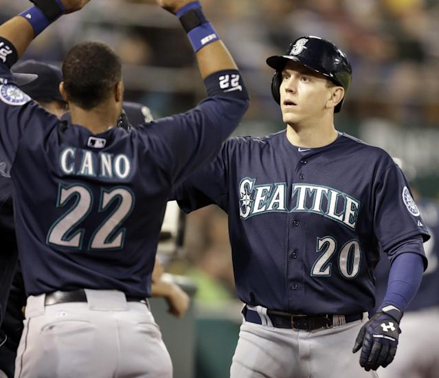 Seattle Mariners' Logan Morrison, right, celebrates with Robinson Cano (22) after Morrison scored against the Oakland Athletics in the fourth inning of a baseball game Tuesday, Sept. 2, 2014, in Oakland, Calif. Morrison scored on a double by Endy Chavez. (AP Photo/Ben Margot)