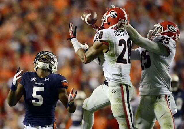 Georgia free safety Tray Matthews (28) and strong safety Josh Harvey-Clemons (25) try to intercept as pass as Auburn wide receiver Ricardo Louis (5) watches late in the fourth quarter of an NCAA college football game at Jordan-Hare Stadium on Saturday, Nov. 16, 2013 in Auburn. Ala. Louis came up with the catch and ran for the game-winning touchdown. Auburn won 43-38. (AP Photo/The Montgomery Advertiser, Amanda Sowards)