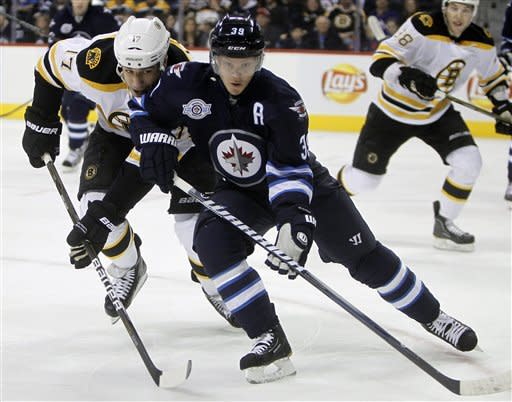 Boston Bruins' Milan Lucic (17) and Winnipeg Jets' Tobias Enstrom (39) battle for the puck during the first period of an NHL hockey game, Friday, Feb. 17, 2012, in Winnipeg, Manitoba. (AP Photo/The Canadian Press, Trevor Hagan)