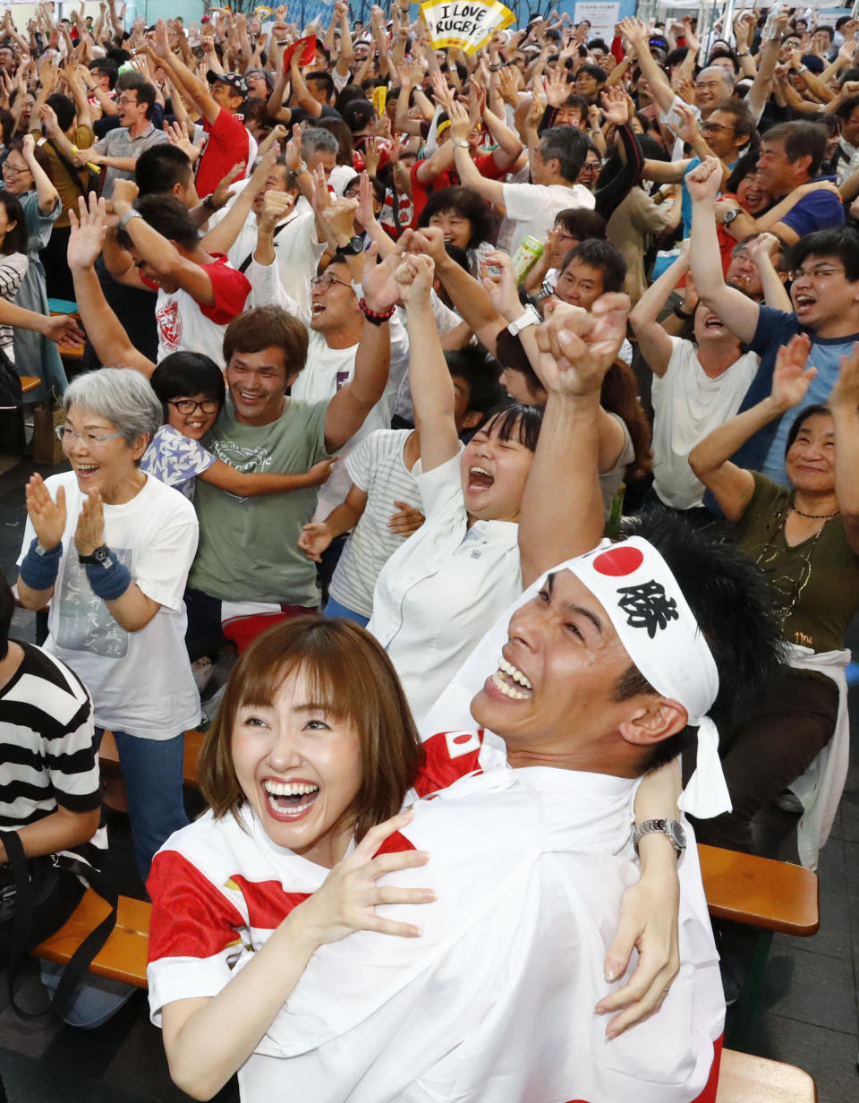 Spectators celebrate after Japan's Kenki Fukuoka scored a try during the Rugby World Cup Pool A game during a public-viewing event in Fukuoka western Japan, Saturday, Sept. 28, 2019. (Takuto Kaneko/Kyodo News via AP)