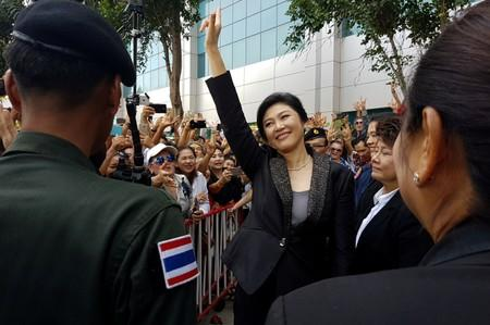 Ousted former Thai prime minister Yingluck Shinawatra greets supporters as she leaves the Supreme Court in Bangkok
