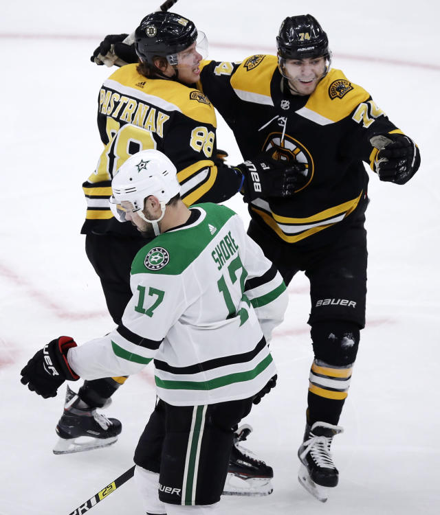 Boston Bruins right wing David Pastrnak, left, celebrates his goal with Jake DeBrusk, right, during the first period of a hockey game in Boston, Monday, Nov. 5, 2018. At foreground is Dallas Stars center Devin Shore (17). (AP Photo/Charles Krupa)