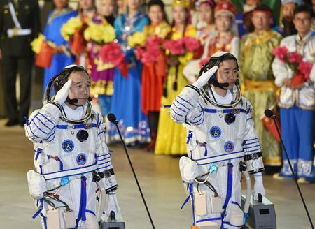 Chinese astronauts Jing Haipeng (L), Chen Dong salute before the launch of  Shenzhou-11 manned spacecraft, in Jiuquan, China, October 17, 2016. China Daily/via REUTERS