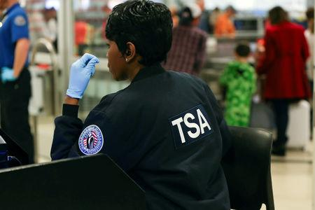 FILE PHOTO - A TSA agent screens passengers at a security checkpoint at Hartsfield-Jackson Atlanta International Airport amid the partial federal government shutdown, in Atlanta