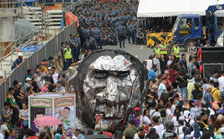 Police block a road leading to congress as anti-government demonstrators display an effigy of Philippine President Rodrigo Duterte