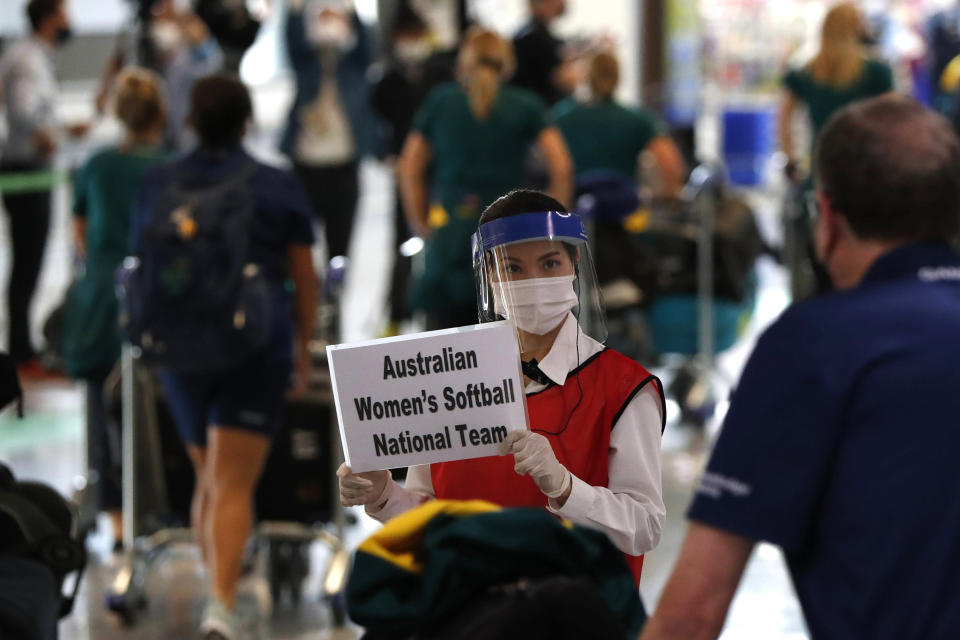 FILE - In this June 1, 2021, file photo, a woman wearing protective mask and face shield greets members of Australia's Olympic softball squad on their arrival at Narita international airport in Narita, east of Tokyo, Japan. The Tokyo Olympics are not looking like much fun: Not for athletes. Not for fans. And not for the Japanese public, who are caught between concerns about the coronavirus at a time when few are vaccinated on one side and politicians and the International Olympic Committee who are pressing ahead on the other. (Issei Kato/Pool Photo via AP, File)