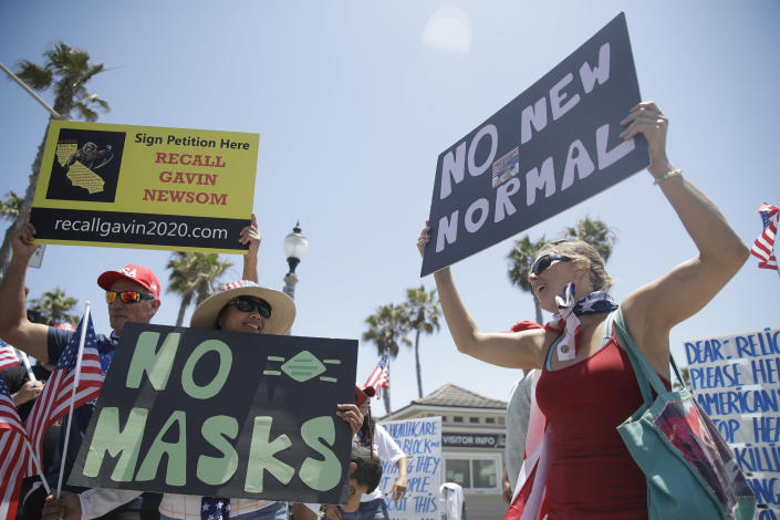 Demonstrators hold signs as they protest the lockdown and wearing masks, June 27 in Huntington Beach, Calif. (Marcio Jose Sanchez/AP)