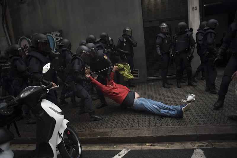 Riot police drag a member of the public away from a school being used as a polling station.