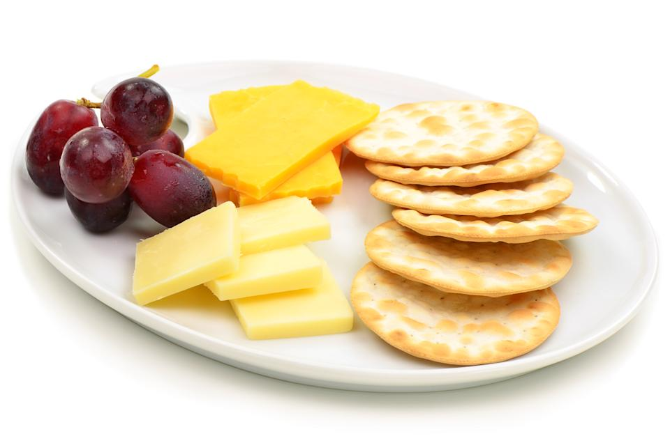 Cheese and crackers with grapes on oval white plate