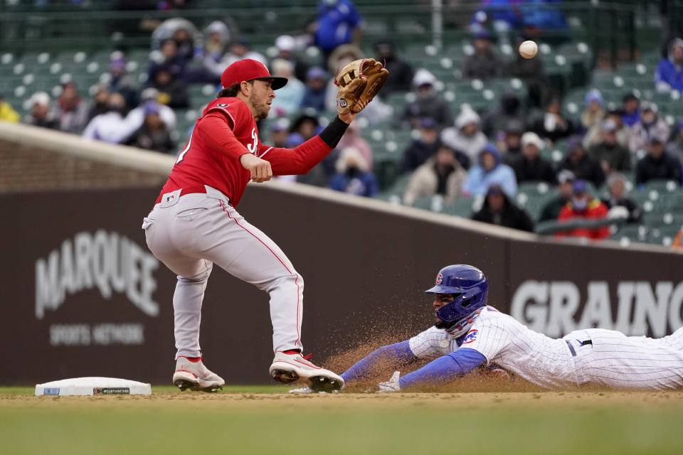Chicago Cubs' Javier Baez slides into second for a steal attempt and is called out by second base umpire Joe West as Cincinnati Reds' Kyle Farmer fields the throw from catcher Tucker Barnhart during the fourth inning of a baseball game Friday, May 28, 2021, in Chicago. The call was overturned after video review. (AP Photo/Charles Rex Arbogast)