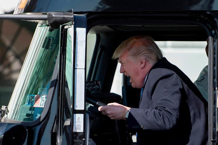 President Donald Trump sits in the drivers seat of a truck as he welcomes truckers and CEOs to the White House in Washington, DC, on March 23, 2017.