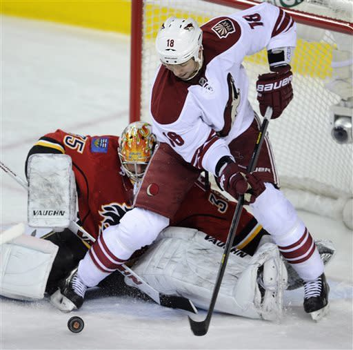 Phoenix Coyotes' David Moss, right, cannot get to the rebound after Calgary Flames goalie Joey MacDonald made a save during second-period NHL hockey game action in Calgary, Alberta, Friday, April 12, 2013. (AP Photo/The Canadian Press, Larry MacDougal)