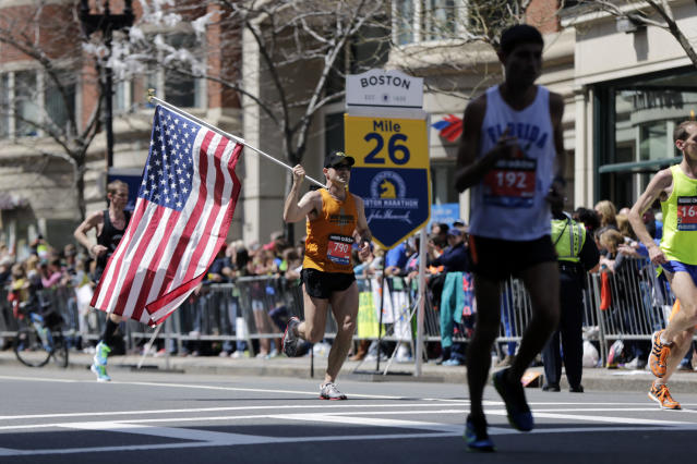Donny Sazama, of Hermantown, Minn., carries an American flag as he runs past the 26 mile mark of the 118th Boston Marathon Monday, April 21, 2014 in Boston. (AP Photo/Robert F. Bukaty)