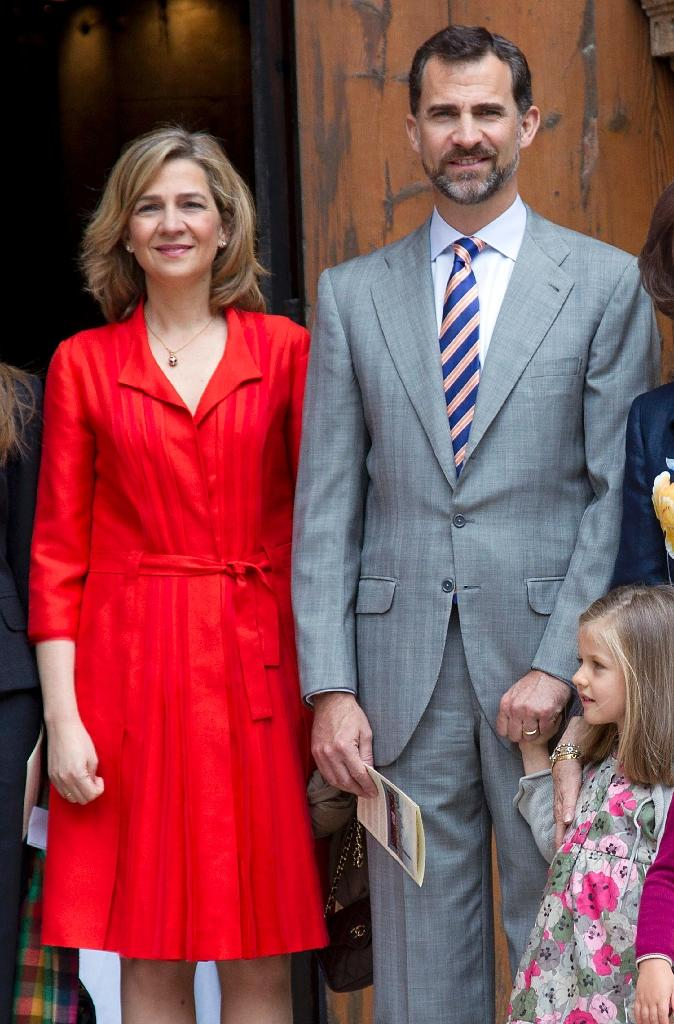 Spain's King Felipe VI (right) stripped the title of Duchess of Palma from his sister Cristina (left), who has been called to stand trial for alleged tax evasion