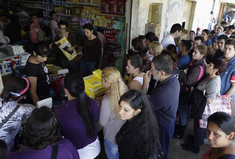 In this June 1, 2013 photo, Paraguayan shoppers buy products in a shop in the town of Clorinda, Argentina, just across the border from Paraguay. Shoppers who turn to the street rather than the banks to swap their dollars are getting a bonanza of extra Argentine pesos and can shop much more cheaply than back at home due to Argentina's currency controls and black market for US dollars. Taking advantage of the guarani's newfound strength, Paraguayans are rolling by the thousands into the Argentine frontier city of Clorinda to do their shopping. (AP Photo/Jorge Saenz)