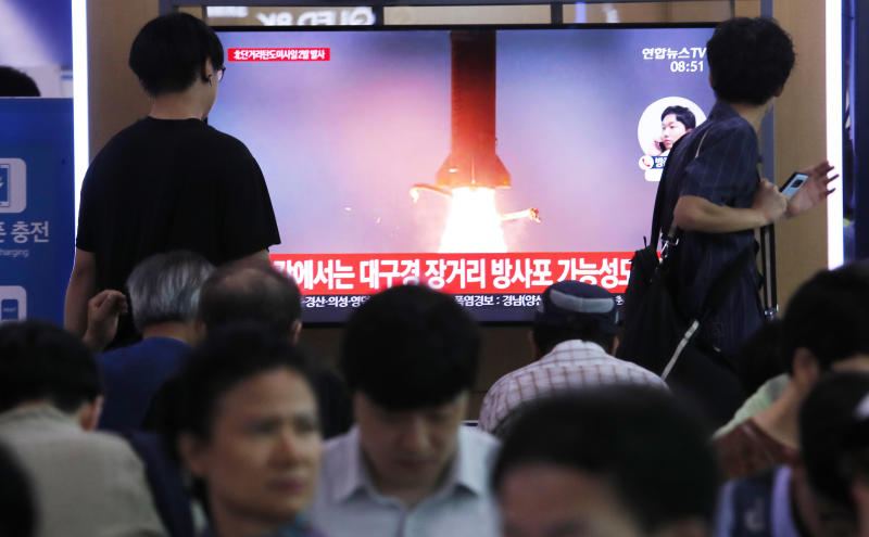 "People watch a TV showing a file image of North Korea's missile launch during a news program at the Seoul Railway Station in Seoul, South Korea, Wednesday, July 31, 2019. North Korea on Wednesday fired several unidentified projectiles off its east coast, South Korea's military said, less than a week after the North launched two short-range ballistic missiles into the sea in a defiance of U.N. resolutions. The signs read: ""Possibility of long-distance multiple rocket launch system."" (AP Photo/Ahn Young-joon)"