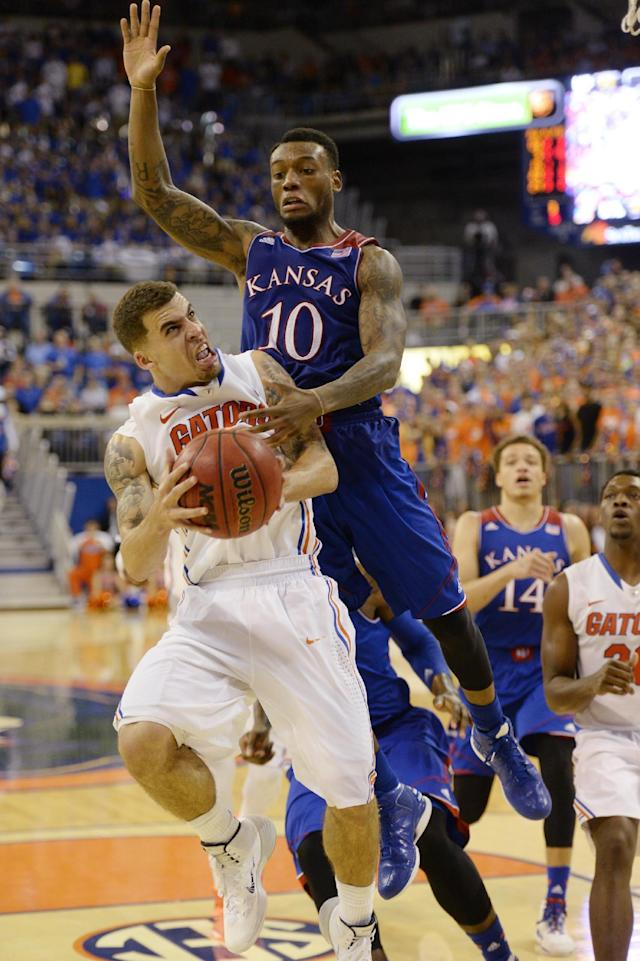 Kansas guard Naadir Tharpe (10) tries to stop Florida guard Scottie Wilbekin (5) during the second half of an NCAA college basketball game Tuesday, Dec. 10, 2013 in Gainesville, Fla. Florida defeated The University of Kansas 67-61. (AP Photo/Phil Sandlin)