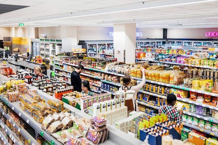 A busy and colorful supermarket with customers shopping for groceries. | Tom Werner—Getty Images&