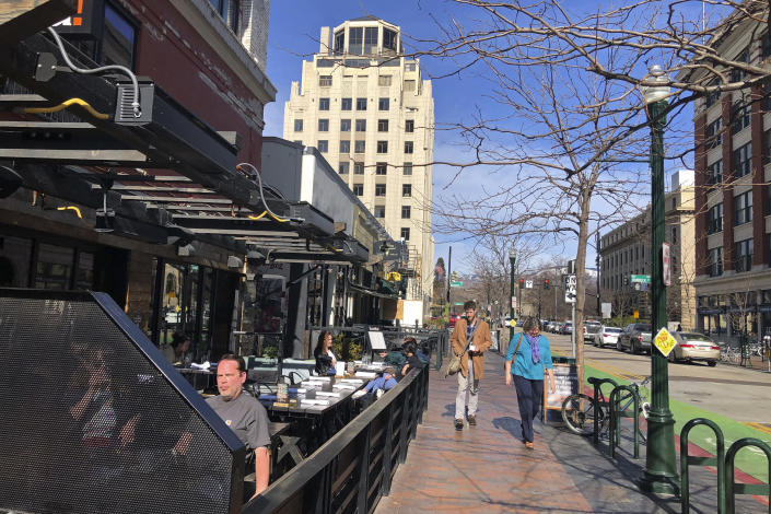In this Wednesday, March 4, 2020, photo, pedestrians and diners enjoy sunny weather in Boise, Idaho. Idaho's presidential primary on Tuesday could give an indication of the political leanings of all the newcomers to the state. The deeply conservative state last year was the fastest-growing in the nation, increasing by 2.1% with nearly 37,000 new residents and approaching 1.8 million. In the last decade, according to the U.S. Census Bureau, Idaho has seen a population jump of more than 200,000. (AP Photo/Keith Ridler)