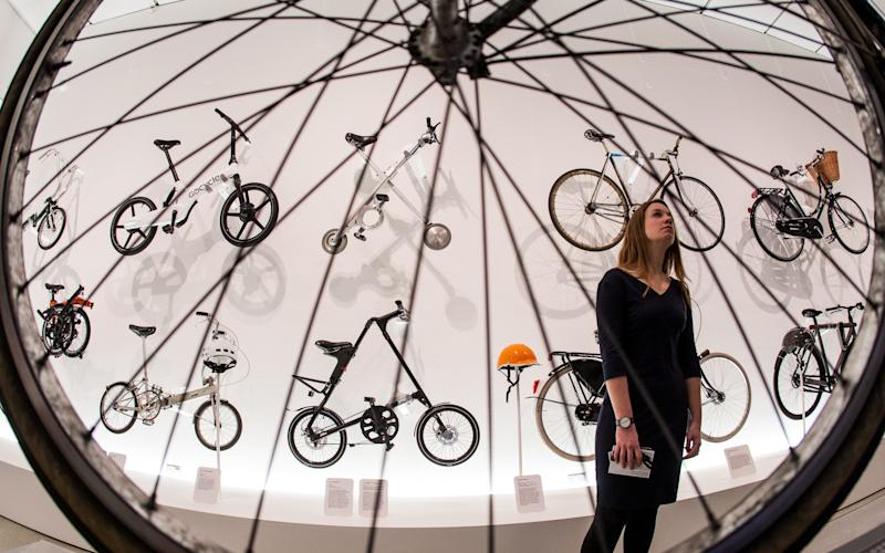 "Design Museum curator Eleanor Suggett looking at bikes of the future exhibited on the walls, including a Sir Clive Sinclair designed ""X-Bike"" - Credit: Julian Andrews/Eye R8 Productions"