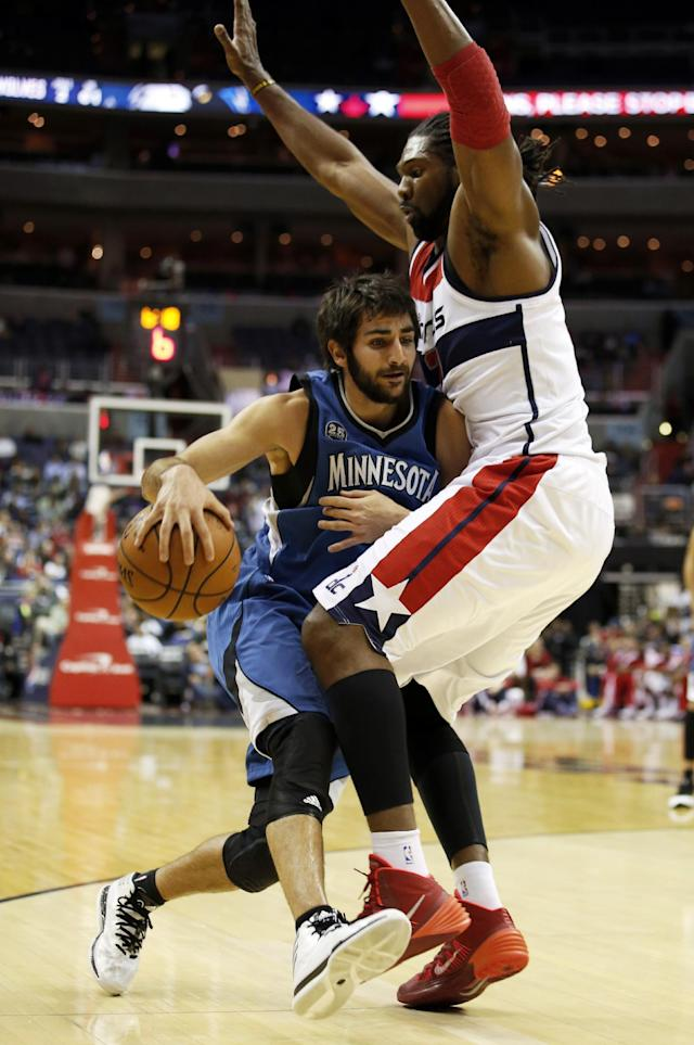 Minnesota Timberwolves guard Ricky Rubio, left, from Spain, runs into Washington Wizards forward Nene, from Brazil, in the first half of an NBA basketball game Tuesday, Nov. 19, 2013, in Washington. (AP Photo/Alex Brandon)