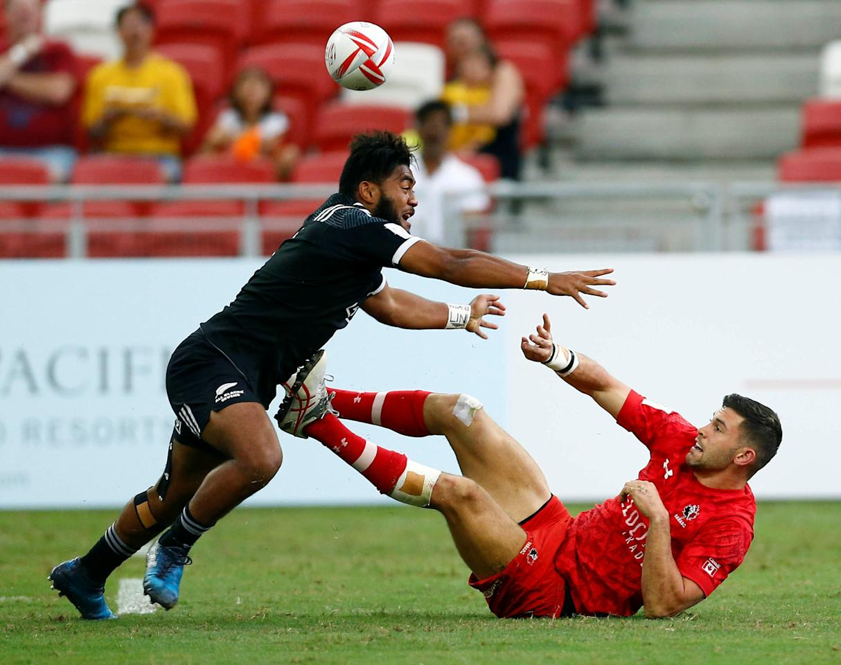 Rugby Union - Singapore Sevens - National Stadium, Singapore - 16/04/17 - Canada's Justin Douglas passes after a tackle from New Zealand's Vilimoni Koroi. REUTERS/Edgar Su
