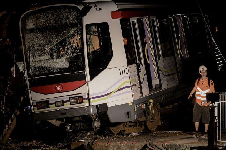 A worker walks past a derailed train in Hong Kong, on May 17, 2013. Over 60 people were injured when a two-car train derailed on Hong Kong's light railway in the north of the city, throwing passengers onto the floor, police said