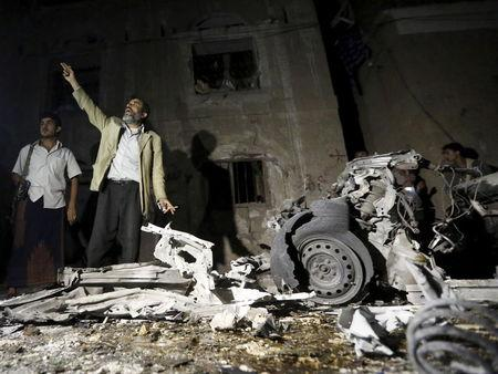 Man reacts as he stands next to wreckage at the site of a car bomb attack outside his house in Yemen's capital Sanaa