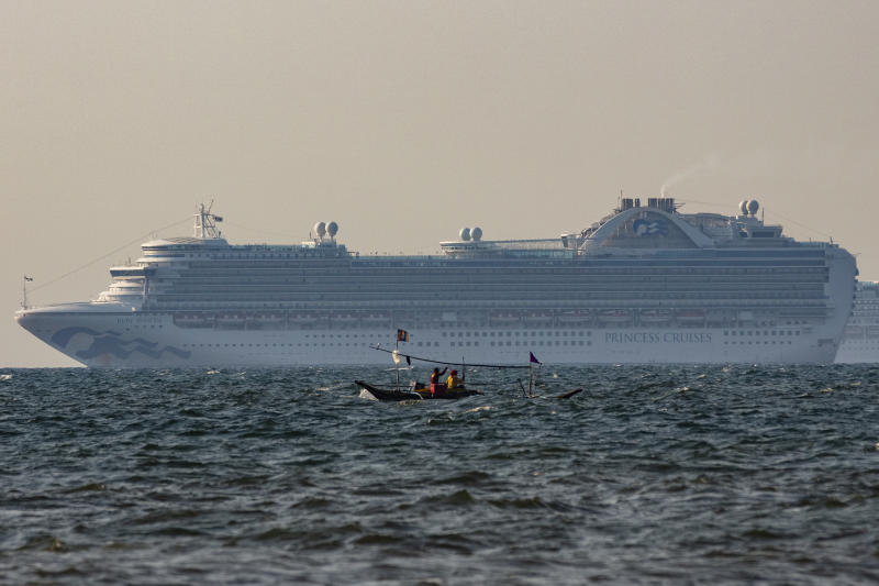 FILE PHOTO: A small fishing boat passes by the cruise ship, Ruby Princess on May 7, 2020 in the waters of Manila Bay, Philippines. The Ruby Princess cruise ship, which is linked to 21 deaths and more than 600 coronavirus (COVID-19) cases, has sailed into Philippine waters on Thursday en route to drop off Filipino crew in Manila. The cruise ship, which is the subject of investigation in Australia, joins at least 16 other cruise ships at anchor waiting for their more than 5,000 Filipino crew to be tested for the coronavirus before disembarking as part of strict quarantine protocols. (Photo by Ezra Acayan/Getty Images)