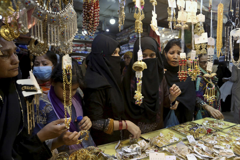 Women ignore social distancing and some do not wear face masks as they shop for the upcoming Eid al-Fitr holiday that marks the end of the Muslim holy fasting month of Ramadan after the government announced new restrictions, in Karachi, Pakistan, Wednesday, May 5, 2021. Pakistani authorities plan to put in place a nine-day lockdown from May 8 to 16 prior to the holiday. (AP Photo/Fareed Khan)