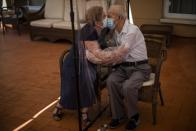 In this Monday, June 22, 2020 photo, Agustina Canamero, 81, and Pascual Pérez, 84, hug and kiss through a plastic film screen to avoid contracting the new coronavirus at a nursing home in Barcelona, Spain. Spain has become the first western Europe to accumulate more than 1 million confirmed infections as the country of 47 million inhabitants struggles to contain a resurgence of the coronavirus. (AP Photo/Emilio Morenatti)