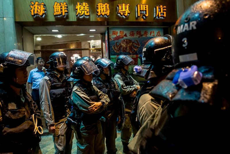 Riot police stand in front of a restaurant while patrolling after an anti-government rally in Hong Kong on August 18, 2019. | Isaac Lawrence—AFP/Getty Images