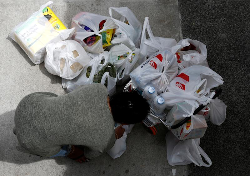 A woman packs her grocery shopping as she stocks up on food supplies outside a supermarket in Singapore on 8 February, 2020. (PHOTO: Reuters)