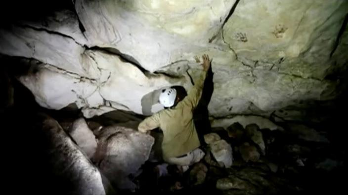 Archeologist Sergio Grosjean explores a cave with hand prints on the walls, in Merida