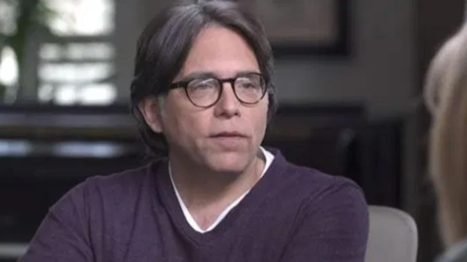 Keith Raniere wearing a purple sweater and round glasses during an interview