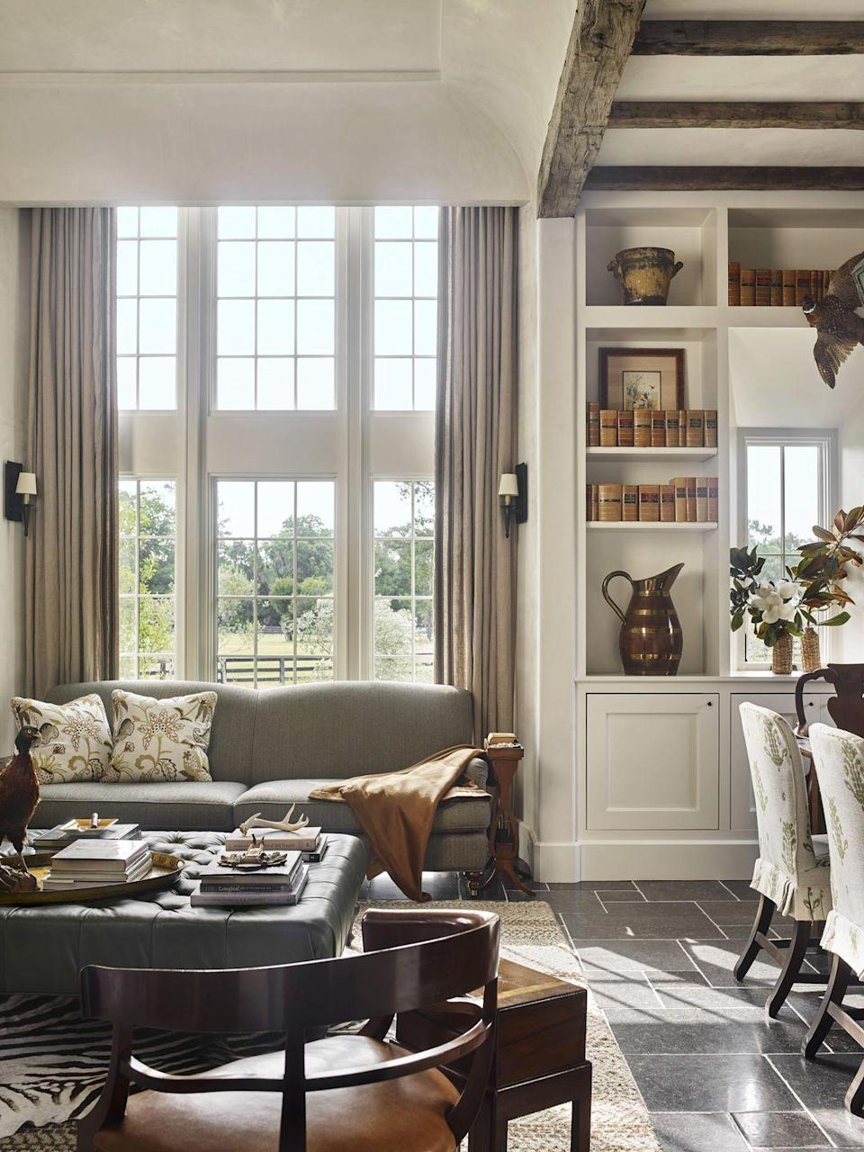 """<p>Webb and Block's coastal Carolina lodge is greatly inspired by the architecture of the British Arts and Crafts movement, and this living room feels reminiscent of a well-traveled Englishman's lair, full of collected items from adventures abroad with design sensibility from his homeland. The <a href=""""http://www.mrshoward.com/"""" rel=""""nofollow noopener"""" target=""""_blank"""" data-ylk=""""slk:Mrs. Howard"""" class=""""link rapid-noclick-resp"""">Mrs. Howard</a> sofa invites one to reflect on the day's wins, while the layered space sparks creativity and dreams of the next getaway. The ottoman leather is <a href=""""https://www.hollyhunt.com/"""" rel=""""nofollow noopener"""" target=""""_blank"""" data-ylk=""""slk:Holly Hunt for Jerry Pair"""" class=""""link rapid-noclick-resp"""">Holly Hunt for Jerry Pair</a> and wool upholstery is <a href=""""https://www.hollandandsherry.com/"""" rel=""""nofollow noopener"""" target=""""_blank"""" data-ylk=""""slk:Holland & Sherry"""" class=""""link rapid-noclick-resp"""">Holland & Sherry</a>.</p>"""