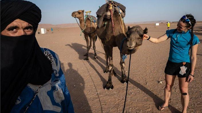 A woman competitor of the Marathon des Sables in the Sahara desert in Morocco is stroking a camel. There is a vast space of sand behind her. A man with a black turban is also in the shot.