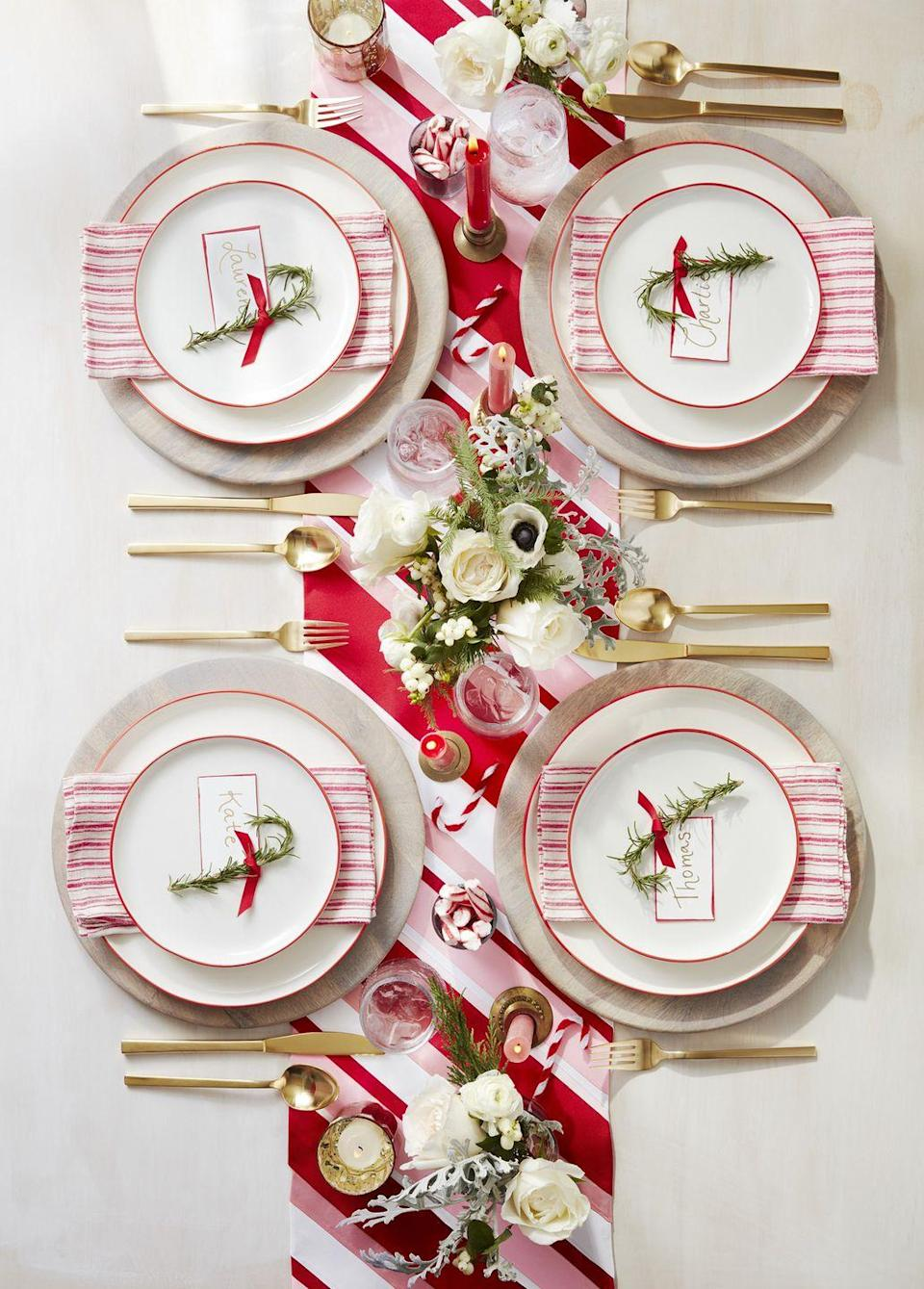 "<p>A candy cane-inspired display makes for the sweetest setup. To make the place cards, bend 7-inch-long pieces of <a href=""https://www.amazon.com/BENECREAT-18-Gauge-Tarnish-Resistant-33-Feet/dp/B077ZPRP1Q?tag=syn-yahoo-20&ascsubtag=%5Bartid%7C10050.g.644%5Bsrc%7Cyahoo-us"" rel=""nofollow noopener"" target=""_blank"" data-ylk=""slk:18-gauge gold wire"" class=""link rapid-noclick-resp"">18-gauge gold wire</a> into a candy cane shape. Attach lengths of rosemary with <a href=""https://www.amazon.com/FISHINGSIR-Monofilament-Fishing-Test-Premium/dp/B07FVQ5S7M?tag=syn-yahoo-20&ascsubtag=%5Bartid%7C10050.g.644%5Bsrc%7Cyahoo-us"" rel=""nofollow noopener"" target=""_blank"" data-ylk=""slk:fishing wire"" class=""link rapid-noclick-resp"">fishing wire</a>. Cut card stock to size and use a <a href=""https://www.amazon.com/Pentel-Touch-Brush-Stroke-SES15C-B/dp/B0081FYWXW?tag=syn-yahoo-20&ascsubtag=%5Bartid%7C10050.g.644%5Bsrc%7Cyahoo-us"" rel=""nofollow noopener"" target=""_blank"" data-ylk=""slk:red brush-tip pen"" class=""link rapid-noclick-resp"">red brush-tip pen</a> to stain edges, then write names with a <a href=""https://www.amazon.com/Pentel-Sunburst-Metallic-Permanent-K908BP2X/dp/B003XQFW9C?tag=syn-yahoo-20&ascsubtag=%5Bartid%7C10050.g.644%5Bsrc%7Cyahoo-us"" rel=""nofollow noopener"" target=""_blank"" data-ylk=""slk:gold pen"" class=""link rapid-noclick-resp"">gold pen</a>. Punch a hole in one corner, thread <a href=""https://www.amazon.com/Topenca-Supplies-Inches-Double-Ribbon/dp/B01ENR4L4Q?tag=syn-yahoo-20&ascsubtag=%5Bartid%7C10050.g.644%5Bsrc%7Cyahoo-us"" rel=""nofollow noopener"" target=""_blank"" data-ylk=""slk:thin red ribbon"" class=""link rapid-noclick-resp"">thin red ribbon</a> through hole, and tie around ""candy cane."" To make the ribbon runner, secure differing widths of <a href=""https://www.amazon.com/Creative-Ideas-Grosgrain-Ribbon-50-Yard/dp/B005G01IOG?tag=syn-yahoo-20&ascsubtag=%5Bartid%7C10050.g.644%5Bsrc%7Cyahoo-us"" rel=""nofollow noopener"" target=""_blank"" data-ylk=""slk:red"" class=""link rapid-noclick-resp"">red</a>, <a href=""https://www.amazon.com/Creative-Ideas-Grosgrain-Ribbon-50-Yard/dp/B005E2X2OA?tag=syn-yahoo-20&ascsubtag=%5Bartid%7C10050.g.644%5Bsrc%7Cyahoo-us"" rel=""nofollow noopener"" target=""_blank"" data-ylk=""slk:white"" class=""link rapid-noclick-resp"">white</a>, and <a href=""https://www.amazon.com/Ribest-Grosgrain-Accessories-Scrapbooking-Decoration/dp/B078YL12TZ?tag=syn-yahoo-20&ascsubtag=%5Bartid%7C10050.g.644%5Bsrc%7Cyahoo-us"" rel=""nofollow noopener"" target=""_blank"" data-ylk=""slk:pink grosgrain ribbon"" class=""link rapid-noclick-resp"">pink grosgrain ribbon</a> on the diagonal to a burlap runner with strips of <a href=""https://www.amazon.com/Mistyfuse-Misty-Yards-Fusible-Webbing/dp/B000PFPSJI?tag=syn-yahoo-20&ascsubtag=%5Bartid%7C10050.g.644%5Bsrc%7Cyahoo-us"" rel=""nofollow noopener"" target=""_blank"" data-ylk=""slk:thin fusible webbing"" class=""link rapid-noclick-resp"">thin fusible webbing</a>. </p><p><a class=""link rapid-noclick-resp"" href=""https://www.amazon.com/AmazonBasics-16-Piece-Stripe-Dinnerware-Service/dp/B00Q5X24XM?tag=syn-yahoo-20&ascsubtag=%5Bartid%7C10050.g.644%5Bsrc%7Cyahoo-us"" rel=""nofollow noopener"" target=""_blank"" data-ylk=""slk:SHOP CHRISTMAS DINNERWARE"">SHOP CHRISTMAS DINNERWARE</a></p>"