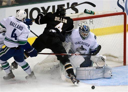 Dallas Stars defenseman Brenden Dillon, center, hits the goalpost while taking a shot on Vancouver Canucks goalie Cory Schneider, right, as Canucks' Keith Ballard, left, defends during the first period of an NHL hockey game on Thursday, April 18, 2013, in Dallas. (AP Photo/Michael Mulvey)