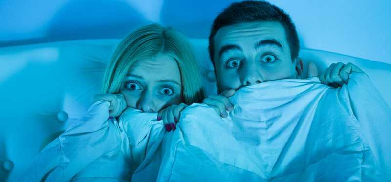 A young couple holds a blanket over their faces in fear.