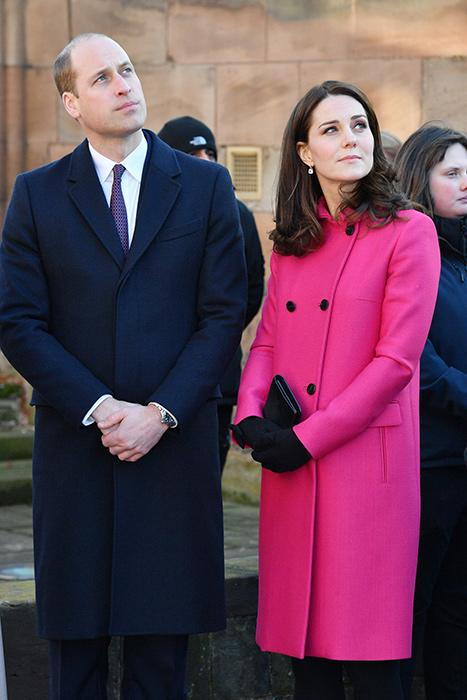Prince William in a dark navy blue topcoat and Kate in a hot pink coat together looking up outside