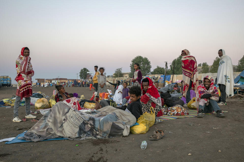 Tigray refugees who fled the conflict in the Ethiopia's Tigray sit up after waking up early in the morning at Hamdeyat Transition Center near the Sudan-Ethiopia border, eastern Sudan, Thursday, Dec. 3, 2020. Ethiopian forces on Thursday blocked people from the country's embattled Tigray region from crossing into Sudan at the busiest crossing point for refugees, Sudanese forces said.(AP Photo/Nariman El-Mofty)