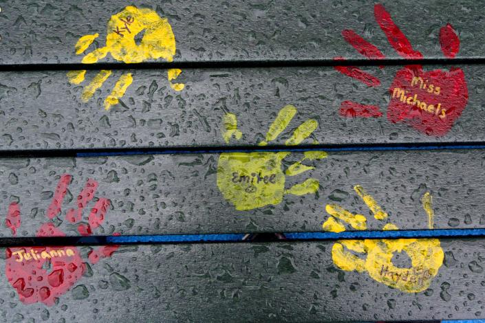 Painted handprints with names of teachers and students are on a playground bench at the new Sandy Hook Elementary School in Newtown, Conn. (Photo: Mark Lennihan/AP)