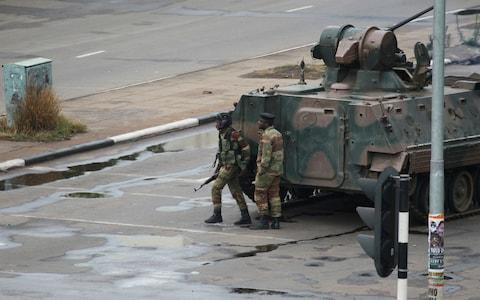 A military tank is seen with armed soldiers on the road leading to President Robert Mugabe's office in Harare on Wednesday morning - Credit: AP