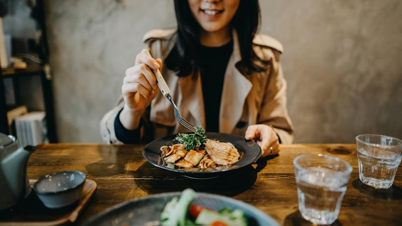 Smiling young woman enjoying dinner date with friends in a restaurant