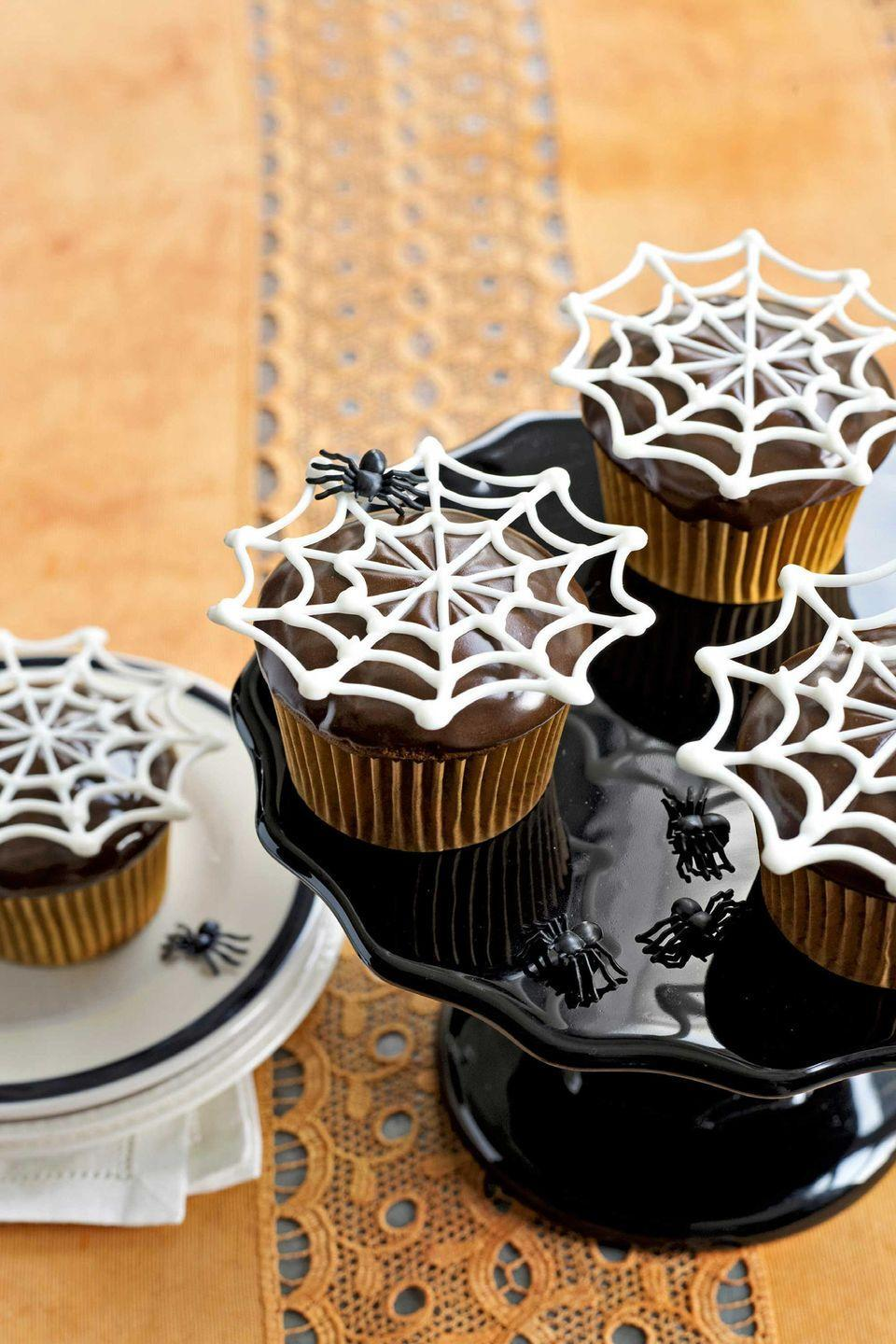 """<p>Super-easy white-chocolate toppers appear to float, Houdini-like, over chocolate cupcakes.</p><p><strong><a href=""""https://www.countryliving.com/food-drinks/recipes/a3015/itsy-bitsy-spiderwebs-cupcakes-recipe/"""" rel=""""nofollow noopener"""" target=""""_blank"""" data-ylk=""""slk:Get the recipe"""" class=""""link rapid-noclick-resp"""">Get the recipe</a>.</strong></p>"""