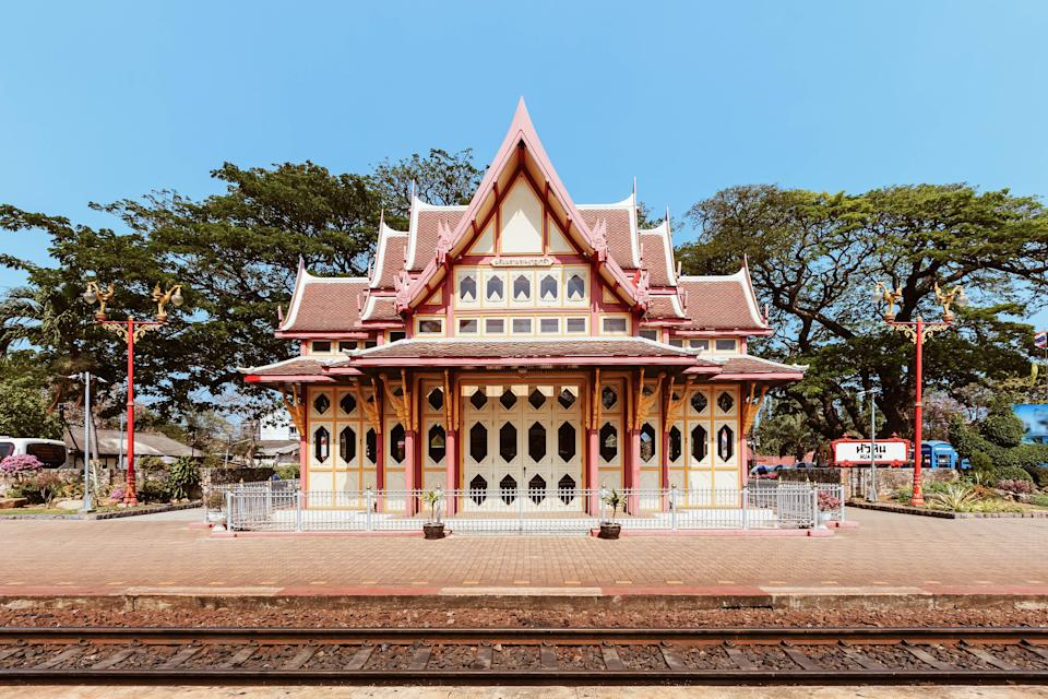 "This is by far the smallest train station on our list, but the Hua Hin train station—located four hours from <a href=""https://www.cntraveler.com/destinations/bangkok?mbid=synd_yahoo_rss"" rel=""nofollow noopener"" target=""_blank"" data-ylk=""slk:Bangkok"" class=""link rapid-noclick-resp"">Bangkok</a> by train—packs the most colorful punch. Decorated in yellow, white, and red, the station features a Thai-meets-Victorian, gingerbread house style of architecture. Across the tracks, the Phra Mongkut Klao Pavilion, pictured, once served as a royal waiting room. While it isn't open to visitors, the building makes for a great photo op. Two train cars and a steam engine are on view outside the station, as well, for railway fans."