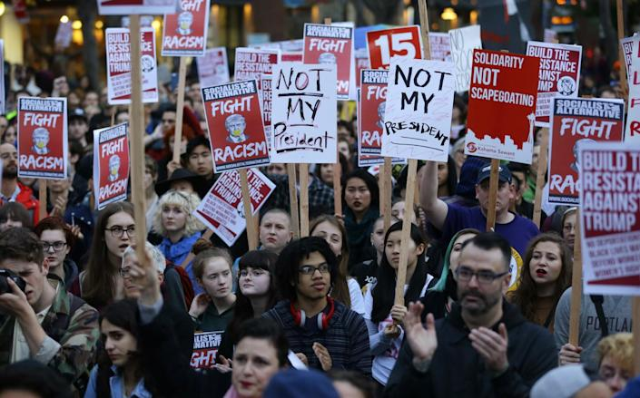 <p>Protesters hold signs during a protest against the election of President-elect Donald Trump, Wednesday, Nov. 9, 2016, in downtown Seattle. (AP Photo/Ted S. Warren) </p>
